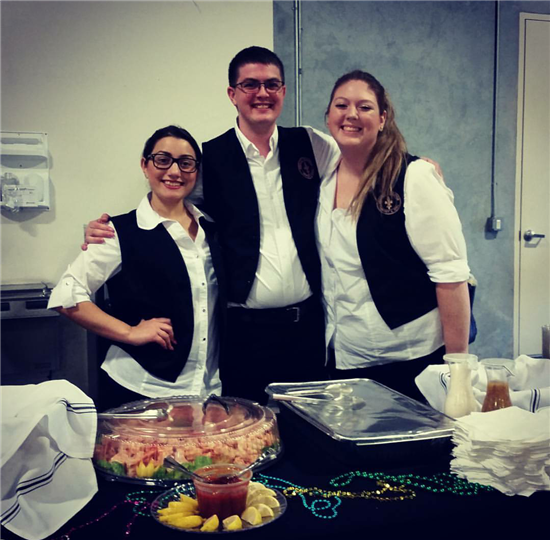 3 employees wearing white dress shirts and black vests, standing behind a catering display decorated with mardi gras decorations