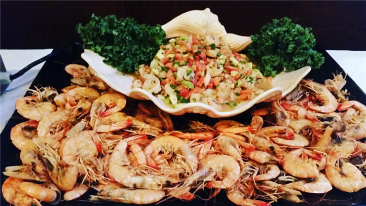 Catering display of a large plate with unpeeled shrimp and ceviche garnished with greens
