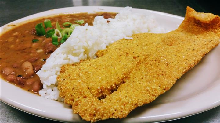 A fried filet of fish with a side of white rice and red beans topped with spring onion