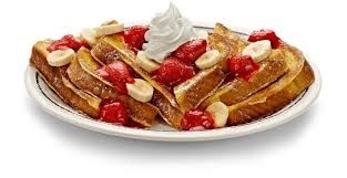 french toast topped with bananas, strawberries and whipped cream