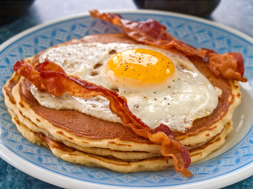 pancakes topped with an egg and bacon