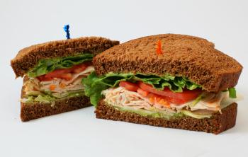 turkey sandwich on wheat bread cut in half with lettuce and tomato