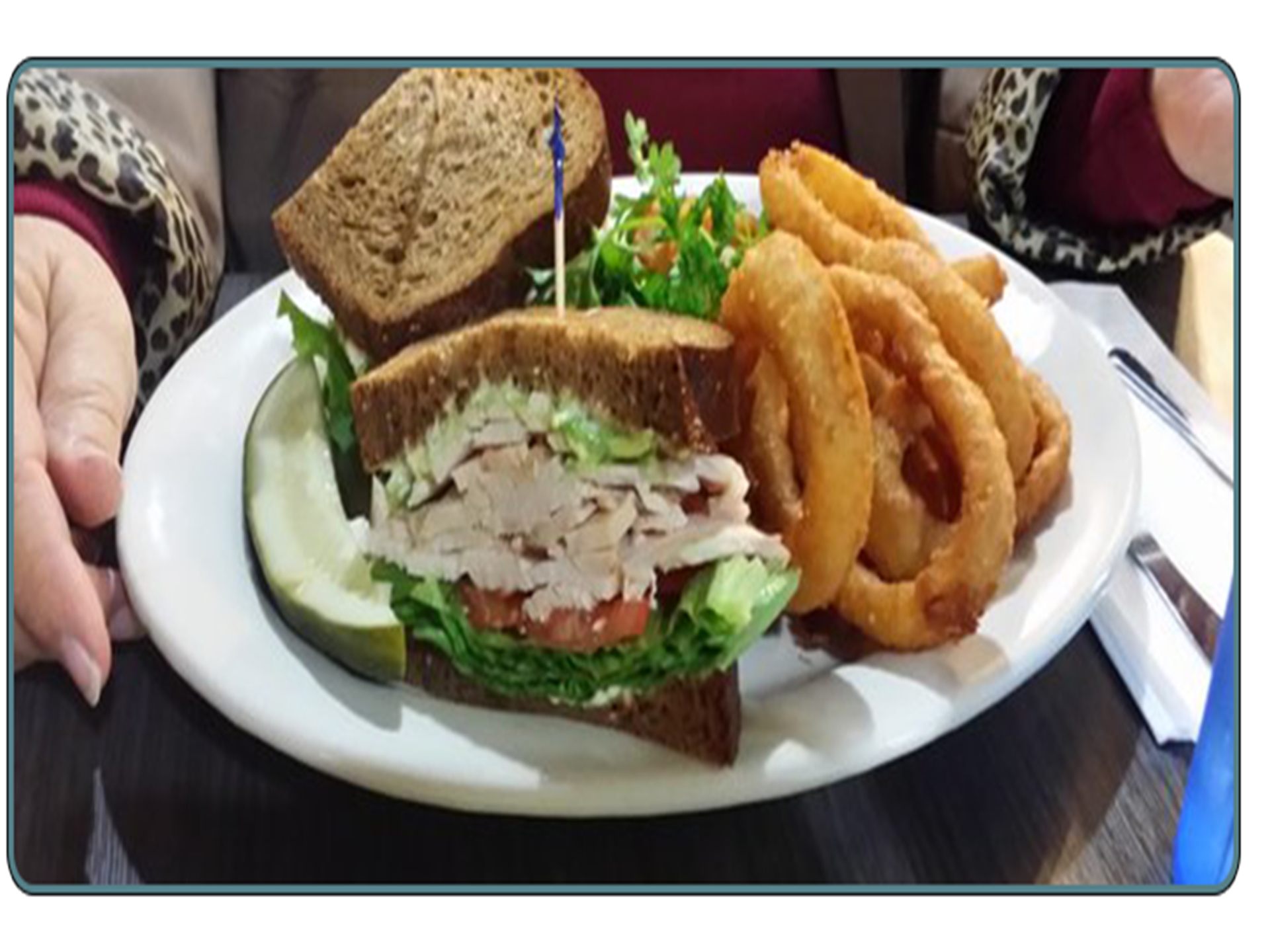 turkey sandwich with lettuce and tomato, onion rings and a pickle on the side