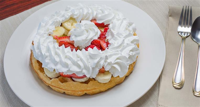 waffle topped with whipped cream, bananas and strawberries