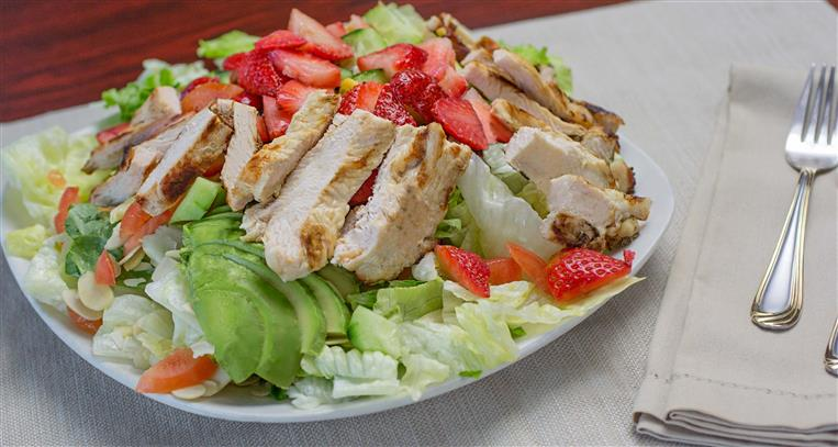 lettuce topped with chicken and strawberries