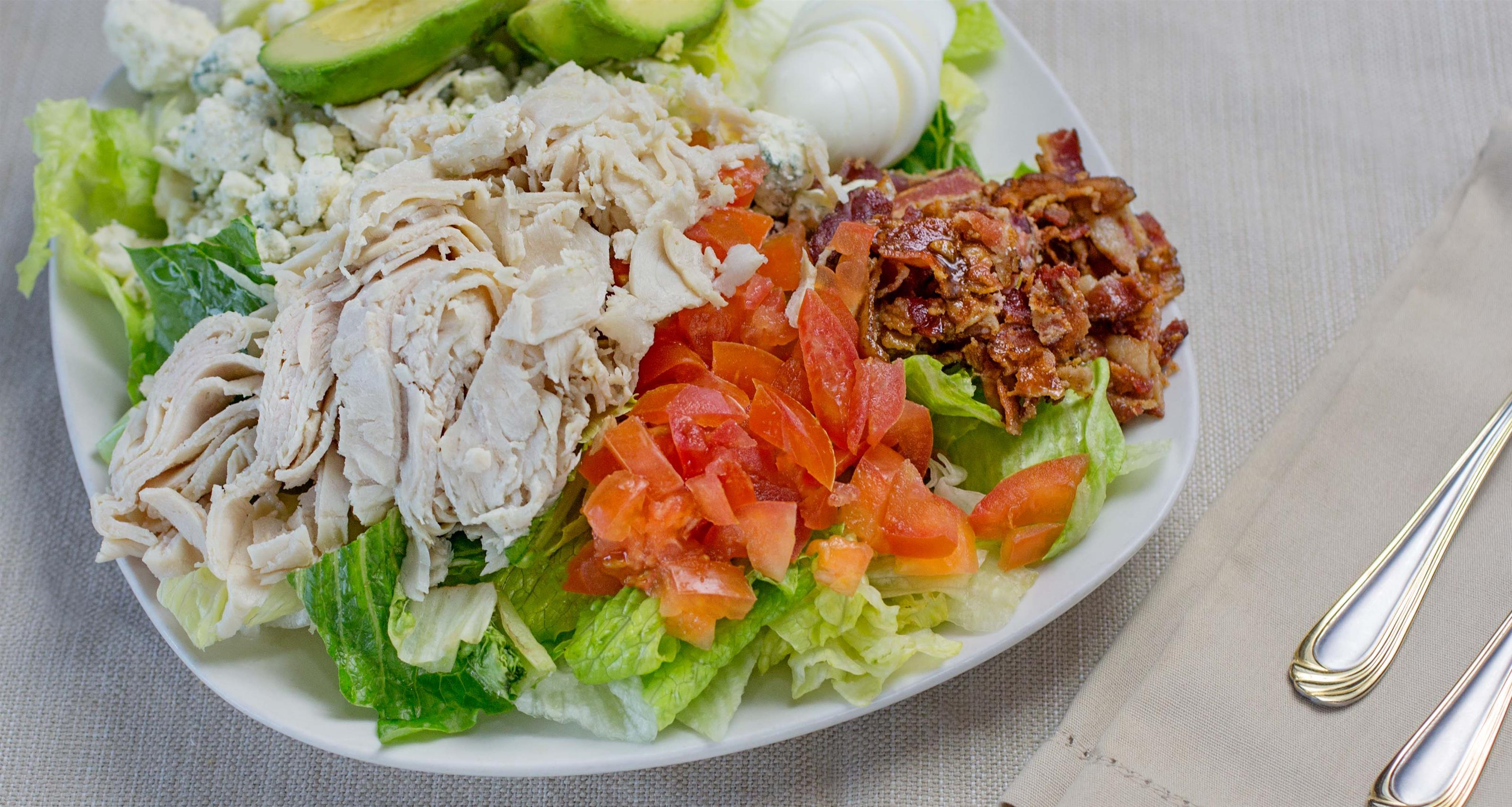 turkey on a plate with bacon bits, lettuce and diced tomatoes
