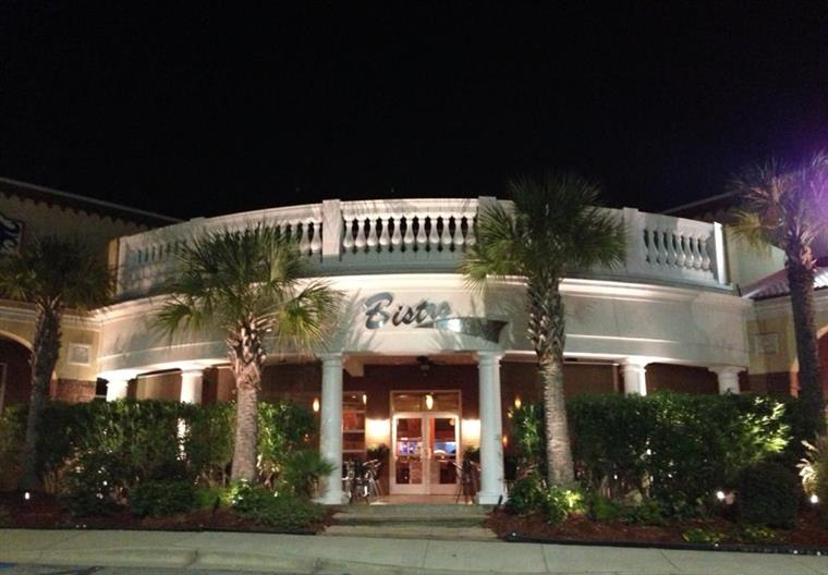 Night time view. Bistro on the boulevard front entrance sign on white facade, tropical trees and shrubbery in foreground