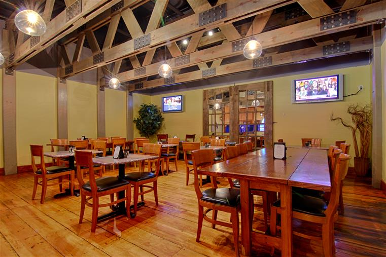 Dining room with wood floors, wood tables and chairs, two TVs on wall, industrial looking wood ceilings