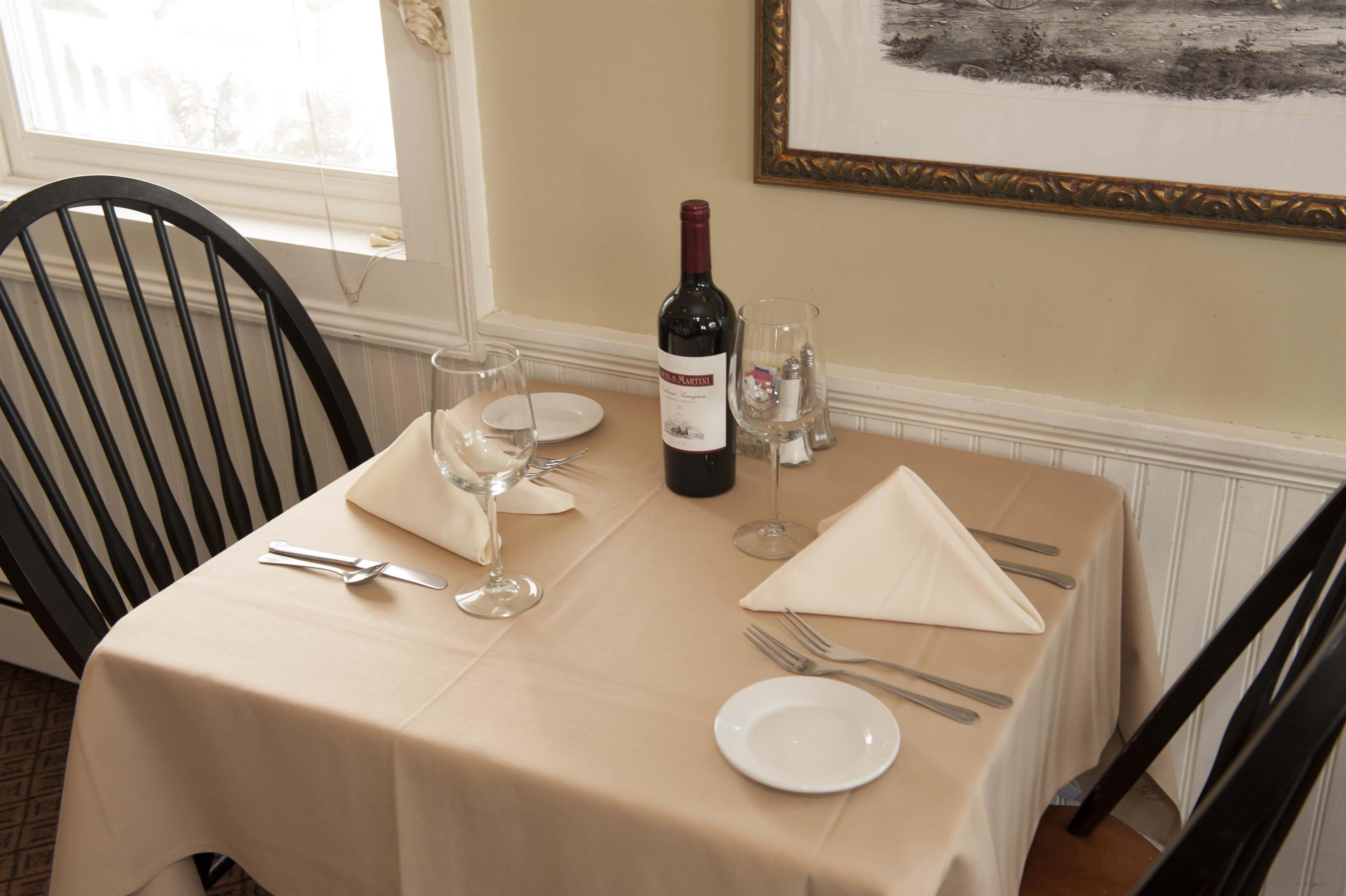 Empty dining room with tables covered in beige tableclothes surrounded by wooden brown and black chairs with wine glasses and a bottle of wine on top