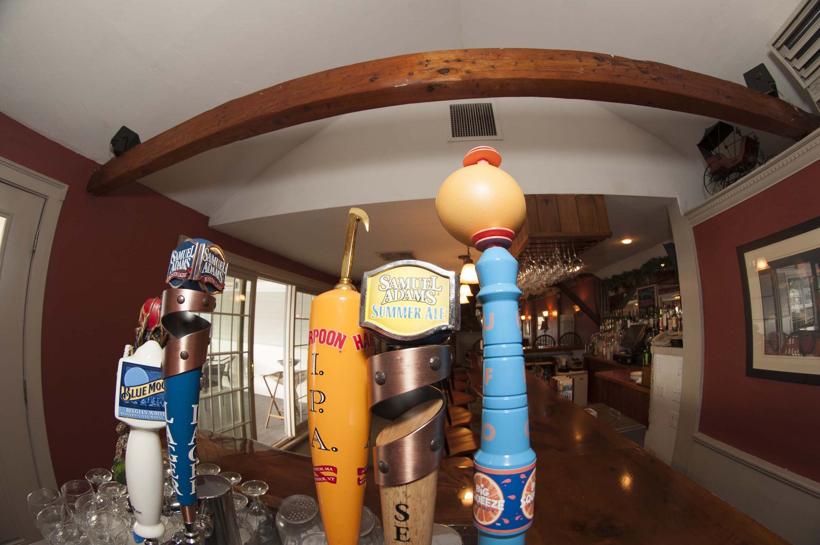 Wooden bar with 5 mulit-colored beer taps overlooking an empty room