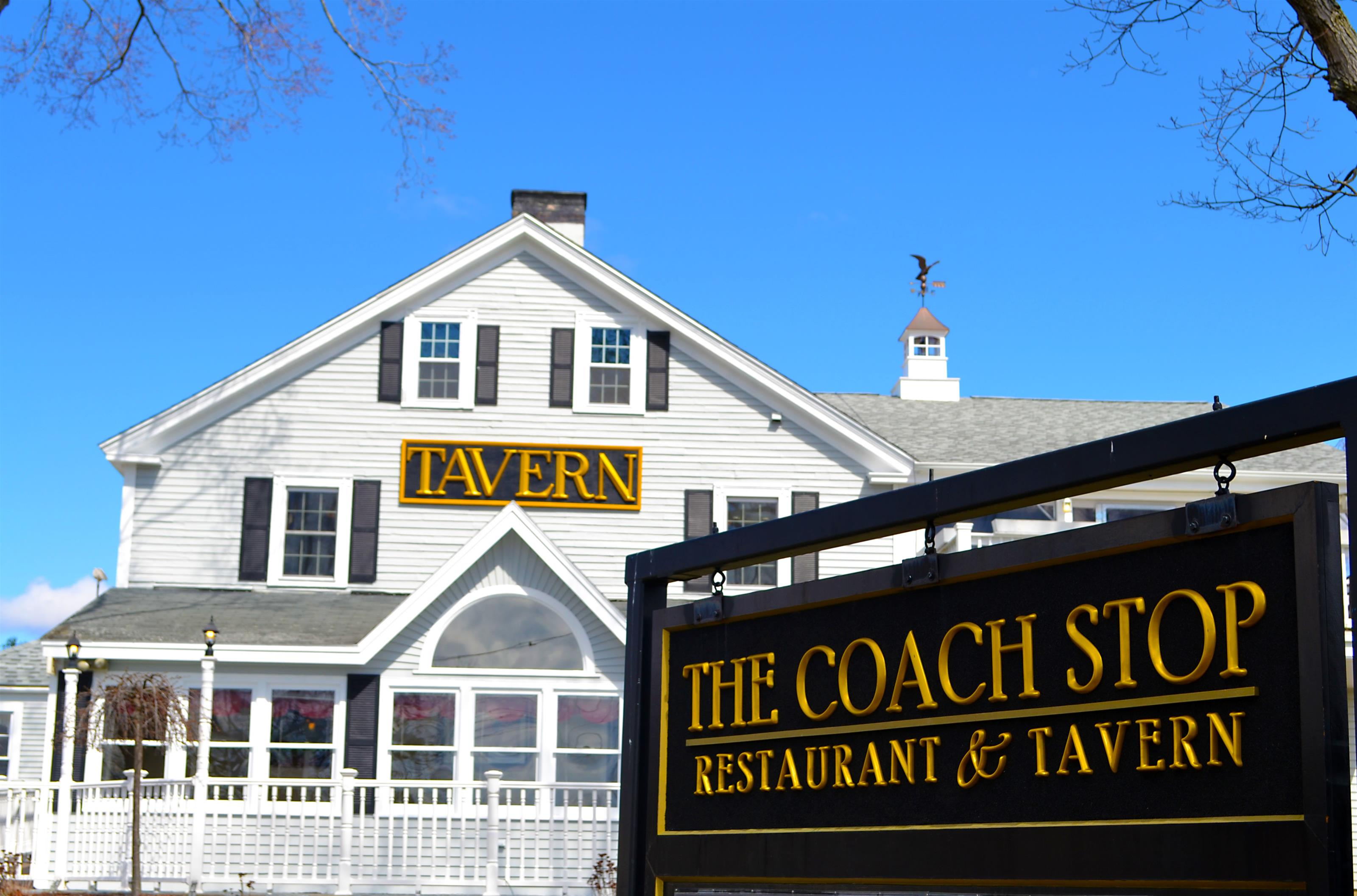 "Exterior of White paneled building with ""Tavern"" sign in middle next to sign saying ""The Coach Stop Restuarant & Tavern"""