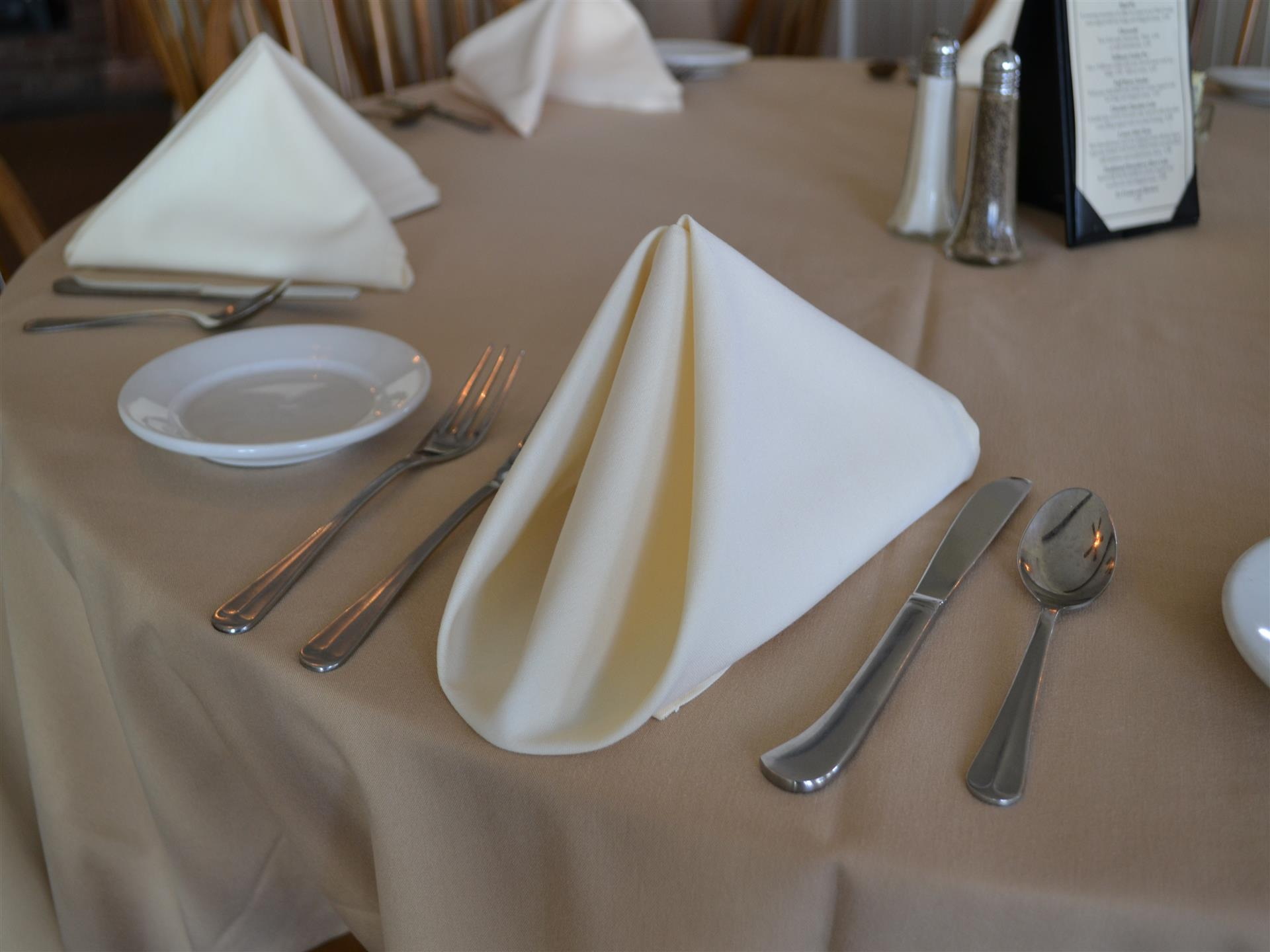 Neatly folded white napkin on a set table