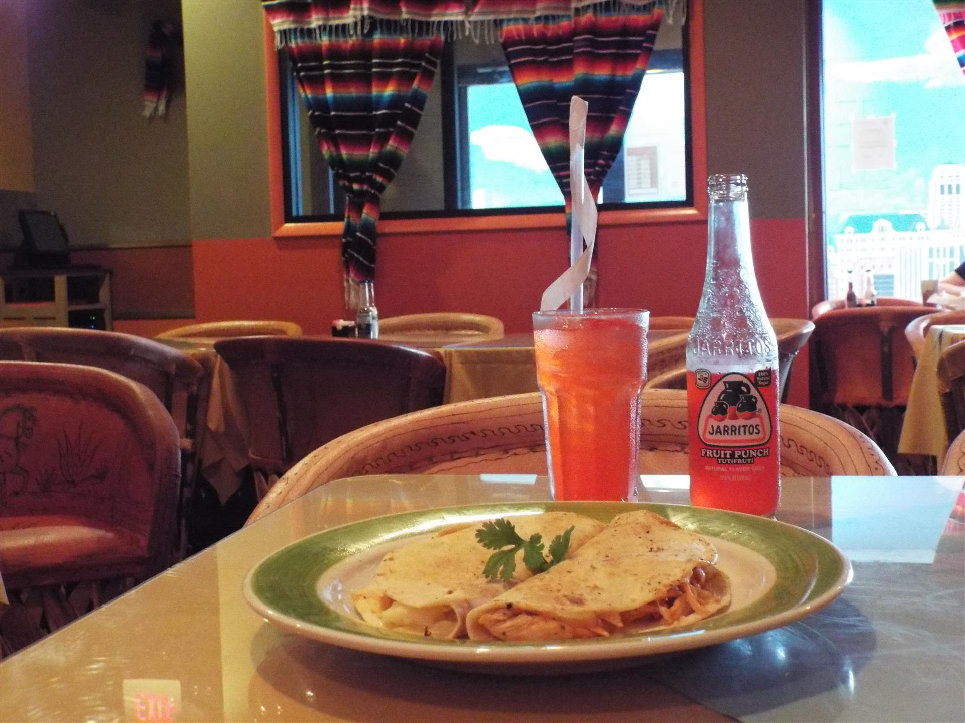 Tortilla on plate next to orange soda