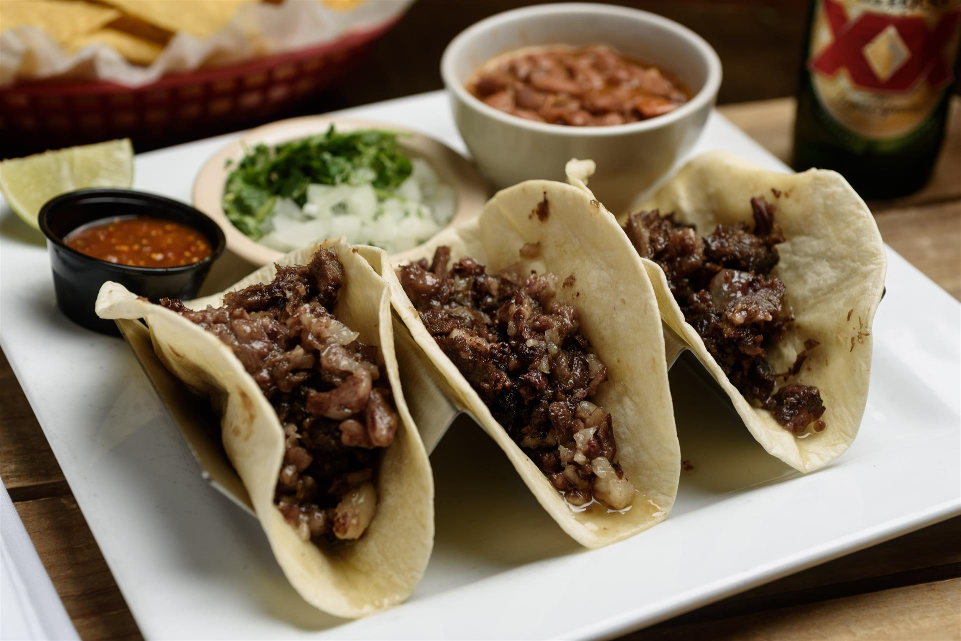 Three soft tacos with steak and onions on a white plate with a cup of salsa, onions, and beans