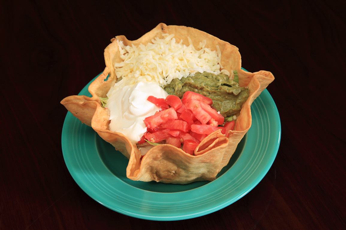 Taco bowl with guacamole, tomatoes, saur cream, and cheese on a green plate