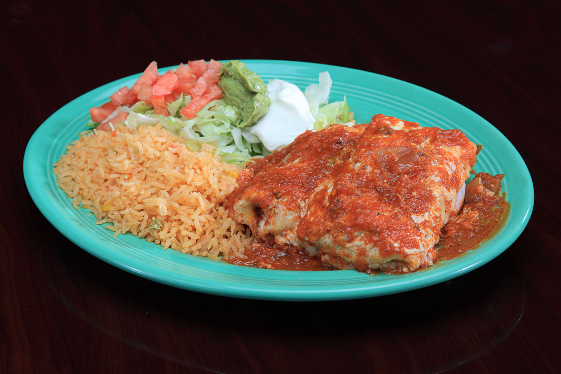 Burrito covered with salsa with guacamole, tomatoes, saur cream, and rice on a green plate