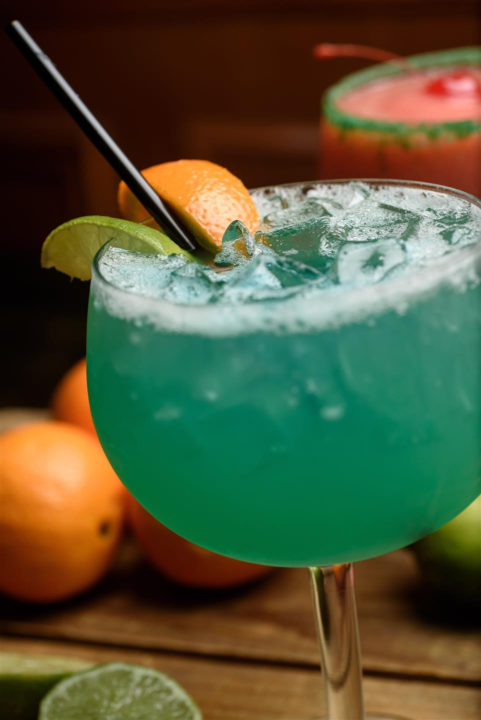 Sapphire blue margarita with lime and orange with black straw