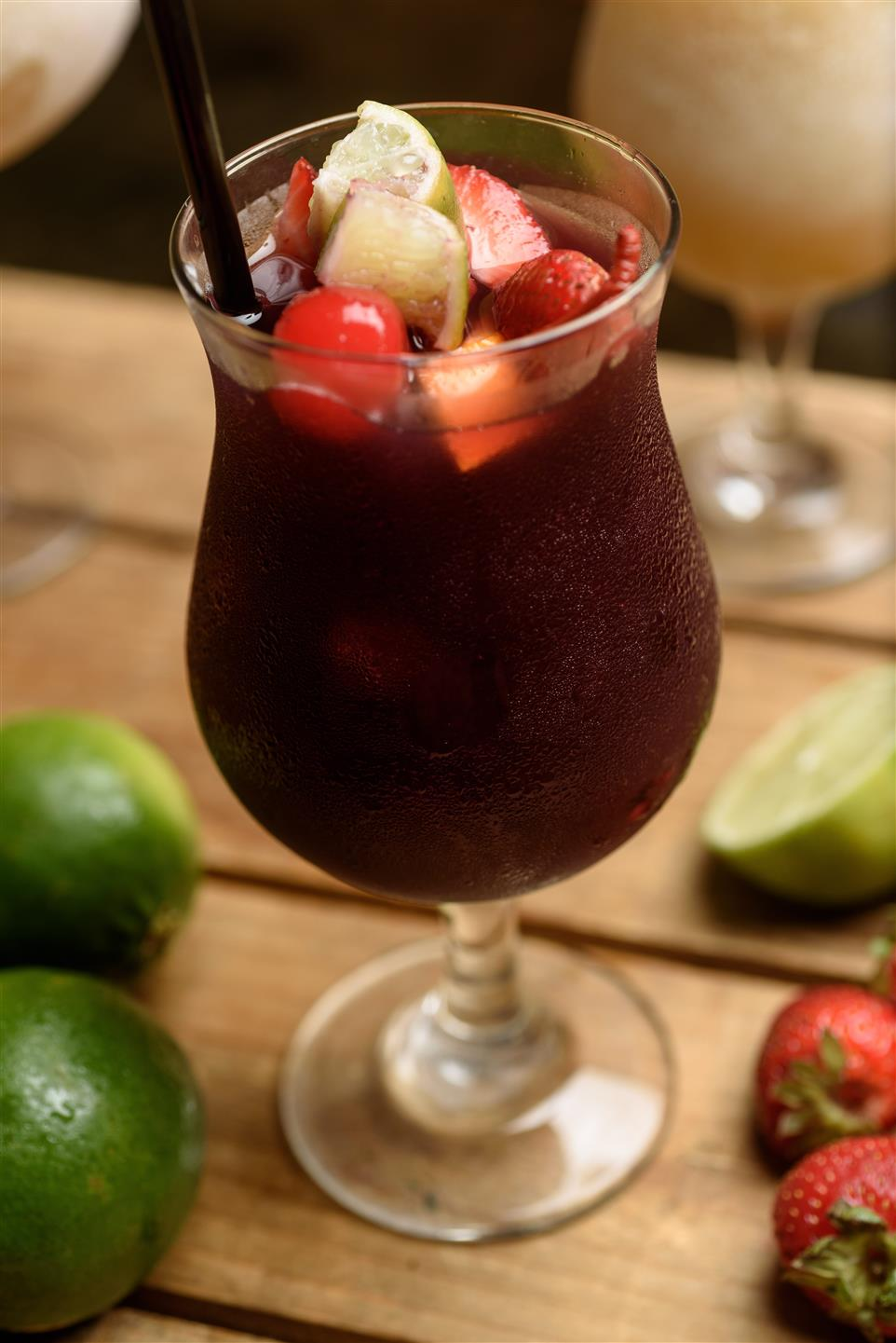Sangria in glass with cherrys, apples, and other assorted fruit