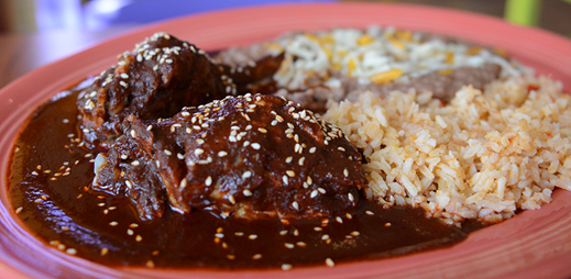 a plate of pork tips in a sauce, with rice on the side