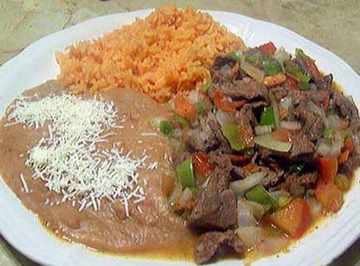 sliced steak with various vegetables, and a side of rice and beans