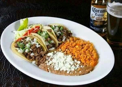 three tortillas with meat and several toppings, with a side of beans and rice