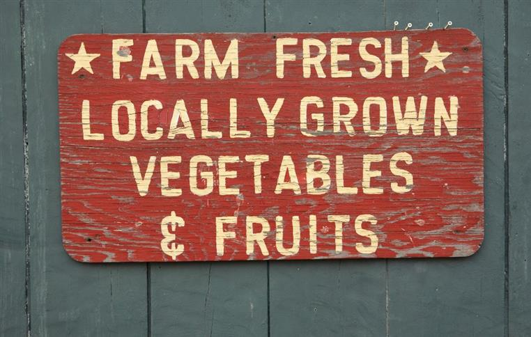 Wood painted sign on wall reading Farm Fresh locally grown vegetables and fruits.