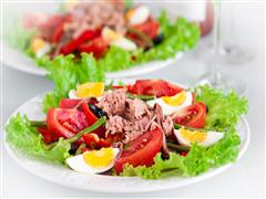 Lettuce, Corn beef, sliced boiled eggs, over greens on a plate.