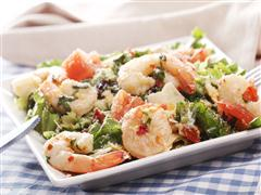 Shrimp scampi over assorted greens.
