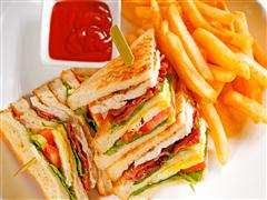 Turkey Club sandwich with french fries and side ketchup