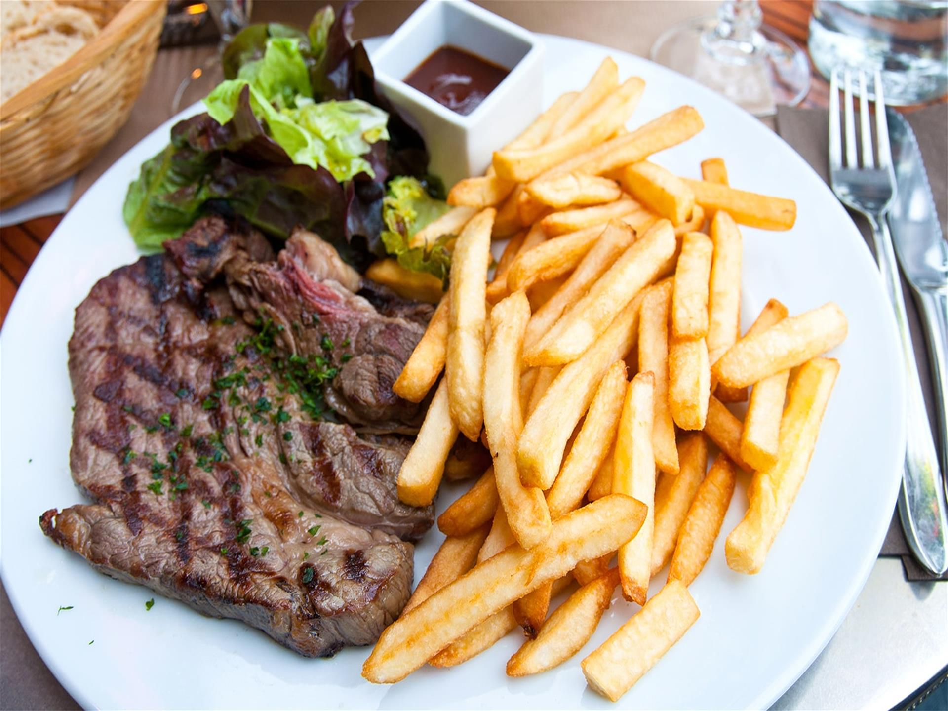 Steak with French Fries and a salad on a white plate