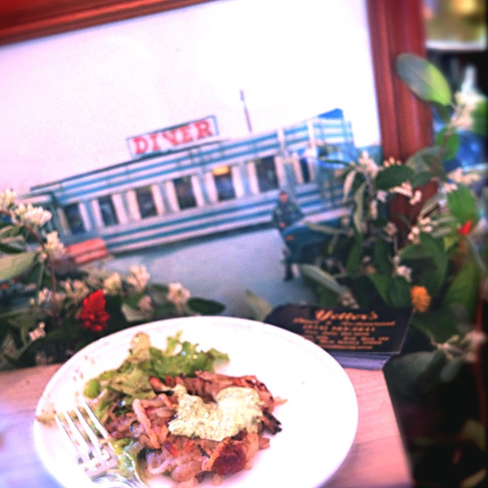 Chicken entree with salad on a white plate, picture of yetters diner in the background.
