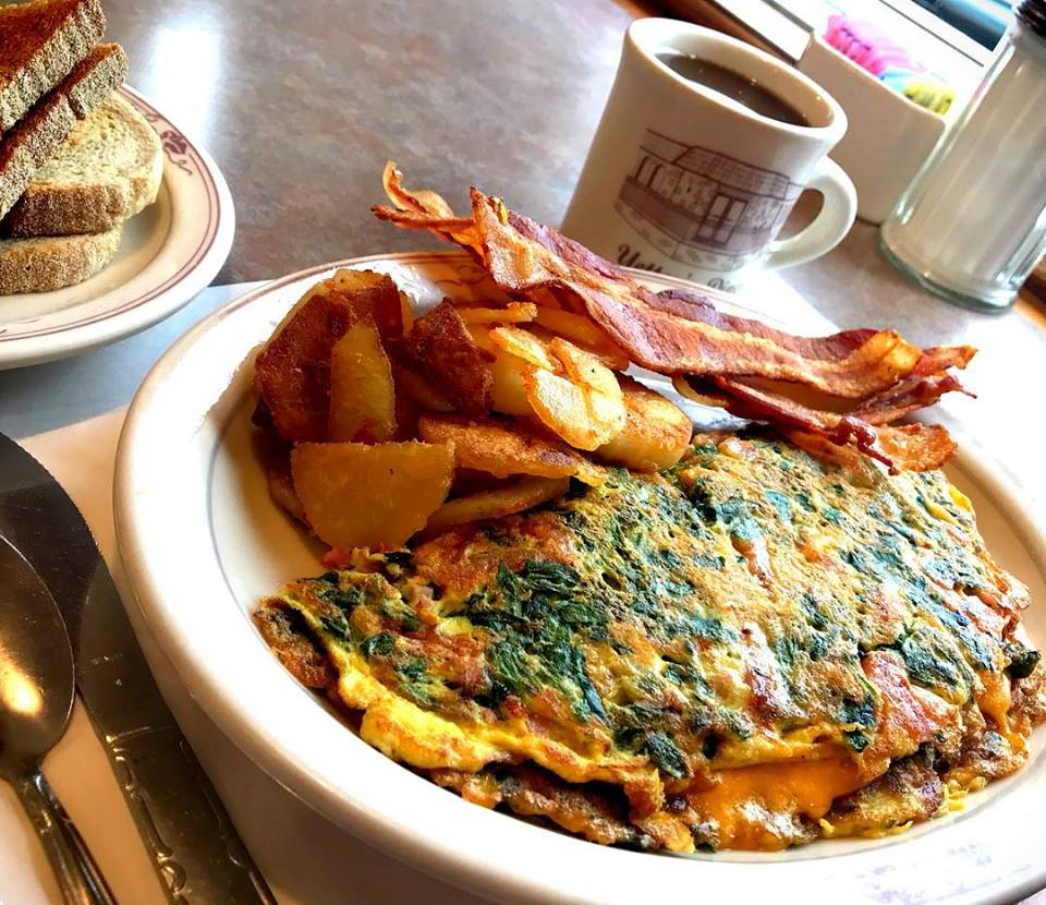 Omelette with spinach, tomato, and cheese with homefries, bacon, and a cup of coffee.