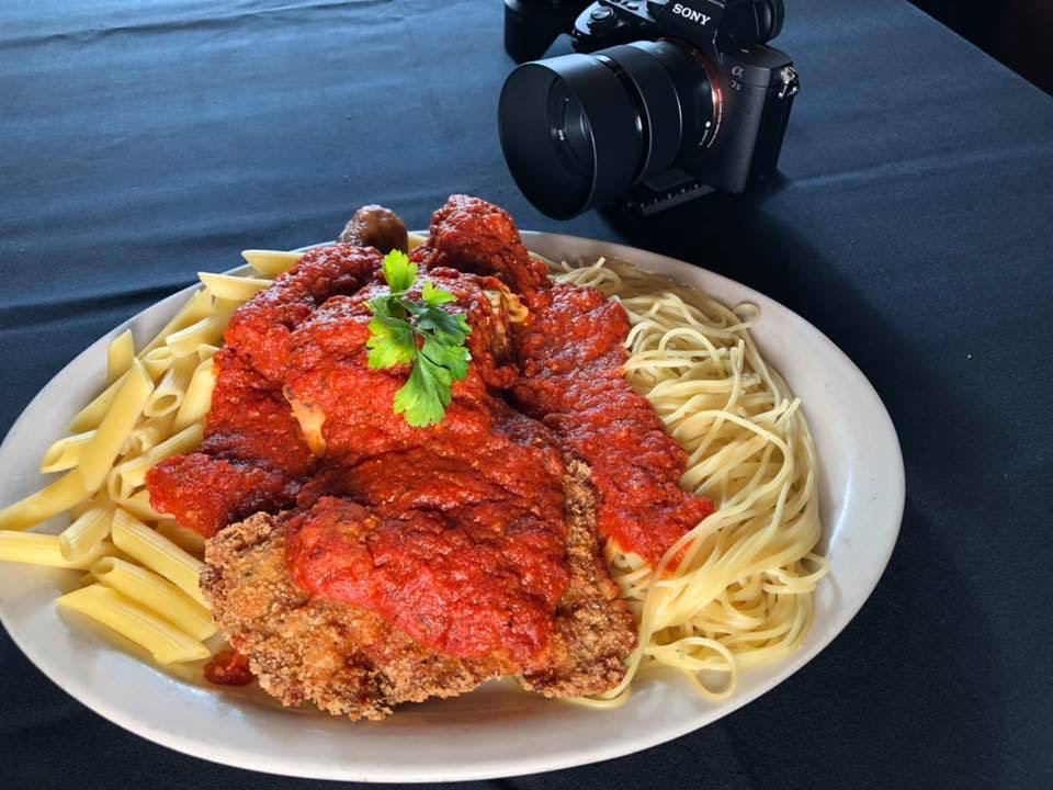 Pasta with red sauce and breaded chicken on a plate with a Sony camera in the background