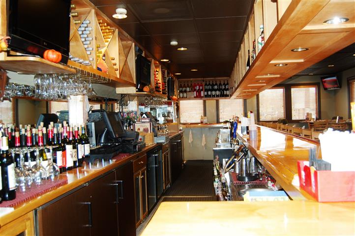 view of behind the bar with bottles of wine and a cash register