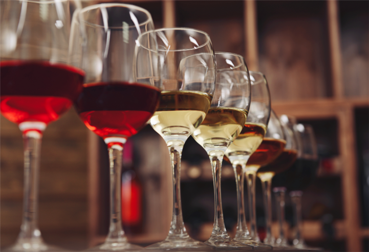 wine glasses line up in a row with both white and red wine