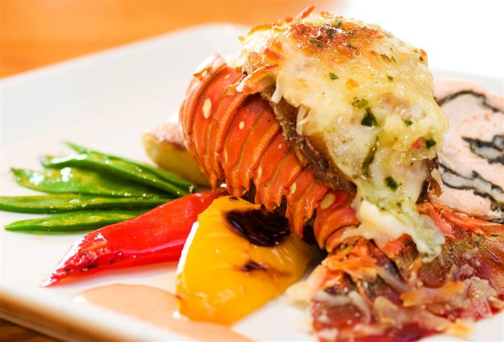 a baked lobster tail with a side of mixed vegetables