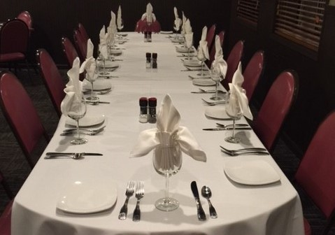 a long table with a table cloth and place settings for a formal event
