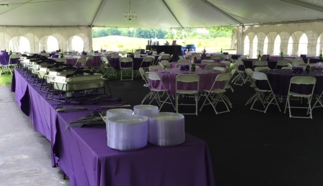 tables and chairs under a tent for an outdoor event