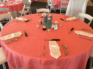 a catering table with place settings and lavender centerpieces