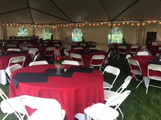 tables and chairs inside a tent for an