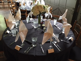 a catering table with place settings and peonies in a centerpiece