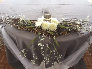 a table with a centerpiece of flowes, leaves, and pine cones with a candle in the middle
