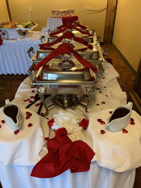 catering table with tin containers holding the hot food and two gravy boats