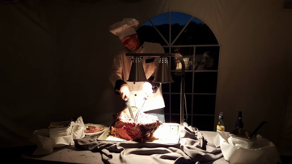 chef cutting at the prime rib station for cateri ng