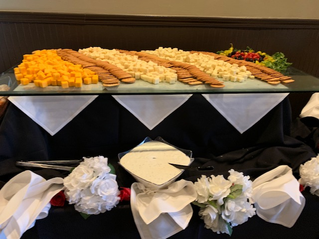 assorted cheeses and crackers on a catering table