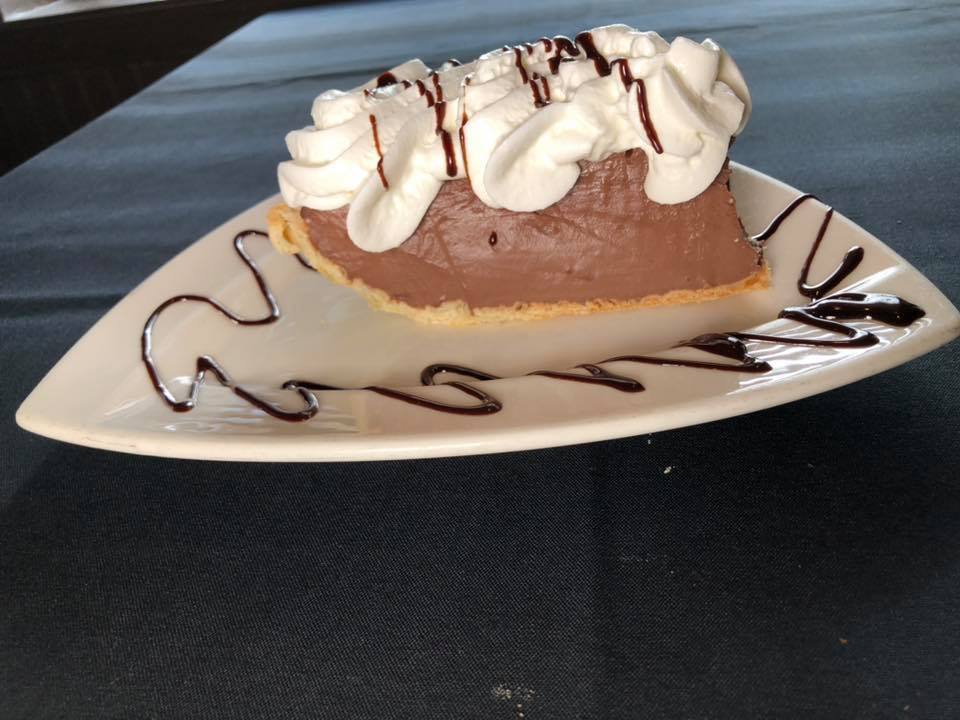 a slice of chocolate mousse pie with whipped cream