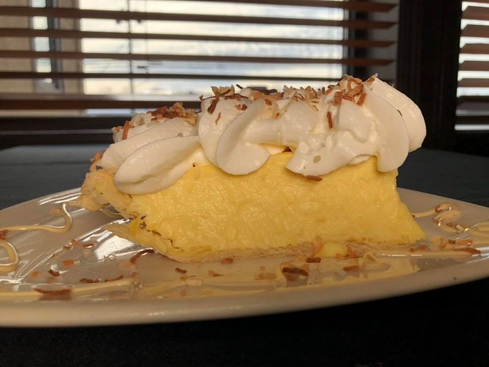 a slice of lemon merigne pie with whipped cream