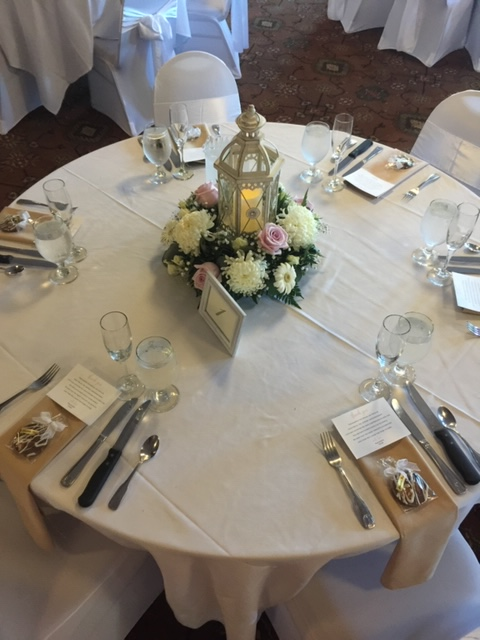 a table with white table cloth, brown place settings, lantern with a candle in it for the centerpiece surrounded by flowers