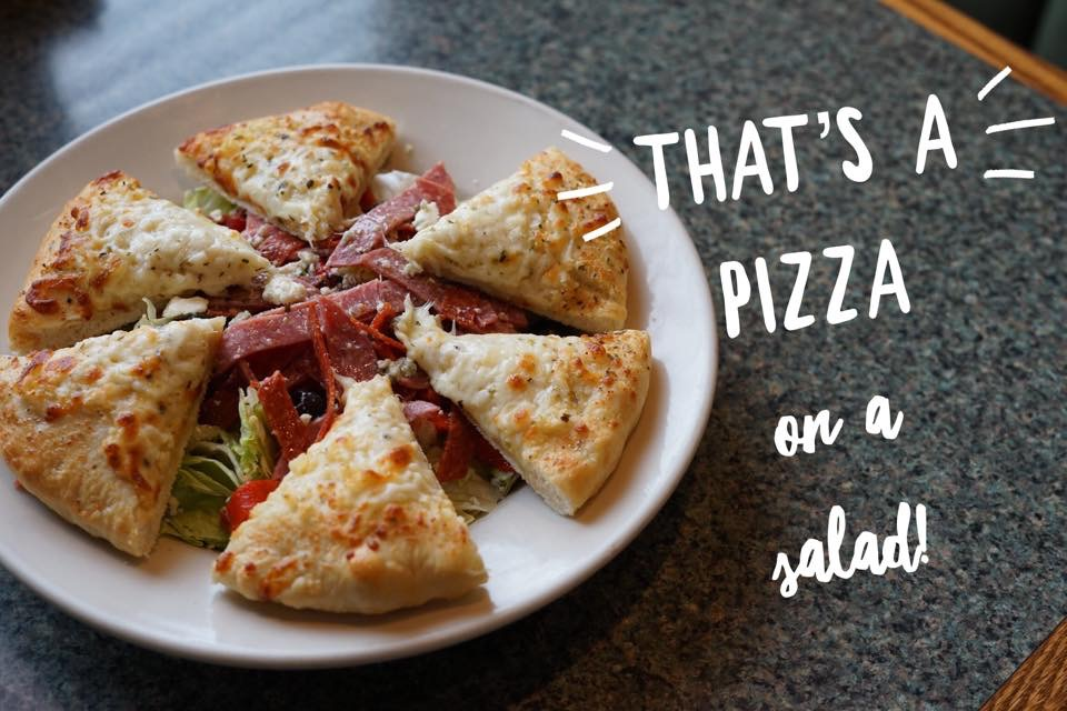"""a salad with pizza on top with the writing """"that's pizza on a salad!"""""""