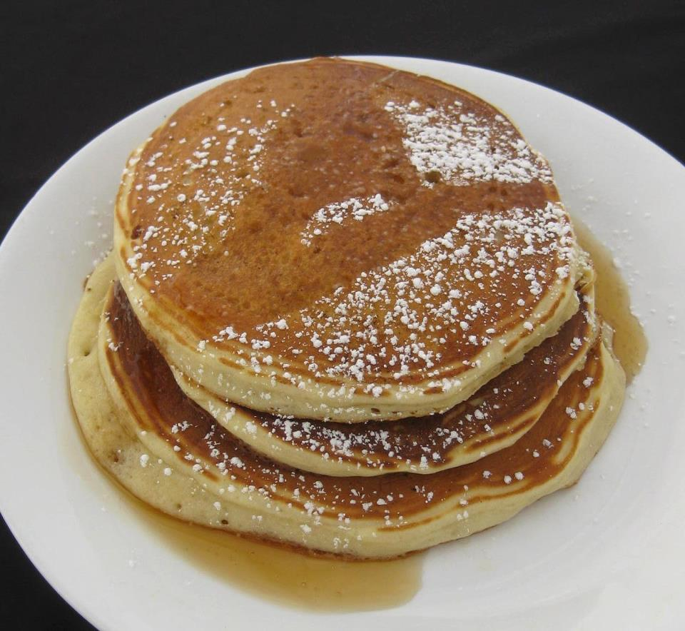 pancakes with powdered sugar and syrup on top